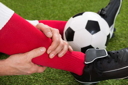 Close-up Of Injured Soccer Player On Field photo