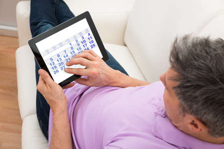 agenda: Close-up Of A Man Looking At Calendar In Digital Tablet Stock Photo