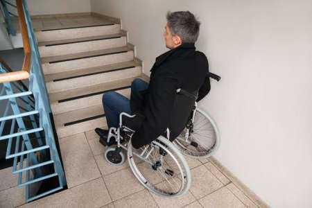 silla de ruedas: Vista posterior de un hombre desactivado en silla de ruedas delante de la escalera