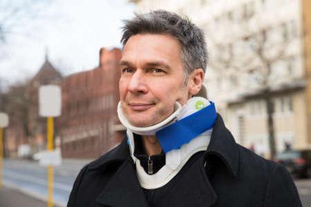 cervicales: Hombre que sufre de dolor de cuello Uso de collar cervical