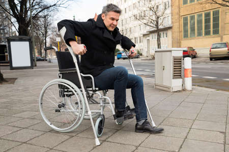 paralysis: Disabled Man Trying To Walk With The Help Crutches