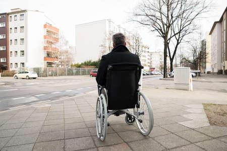 discapacidad: Vista trasera de un hombre discapacitado en silla de ruedas Mirando a la calle