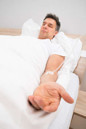 catheters: Patient Resting On Bed With Iv Drip In Hospital Stock Photo