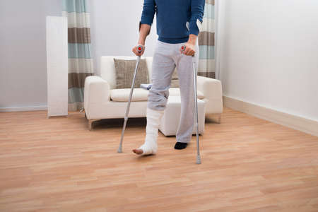 adult bones: Low Section Of A Disabled Man Using Crutches For Walking Stock Photo