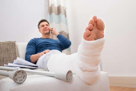 plaster: Man With Fractured Leg Sitting On Sofa Talking On Cellphone Stock Photo