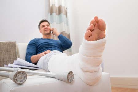 plaster leg cast: Man With Fractured Leg Sitting On Sofa Talking On Cellphone Stock Photo