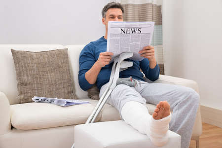 bandaged: Disabled Man With Crutches Sitting On Sofa Reading Newspaper Stock Photo