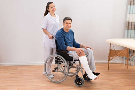 cast: Nurse Assisting Disabled Patient Sitting On Wheelchair Stock Photo