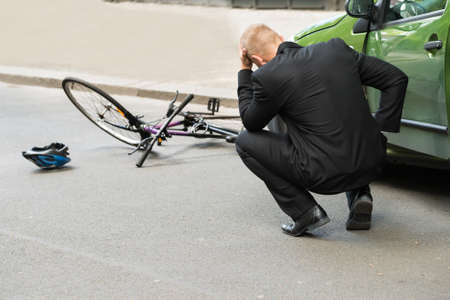 bicicleta: Triste conductor masculino después de la colisión con la bicicleta en la carretera Foto de archivo