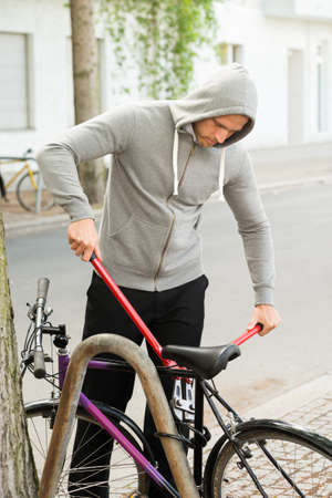 looting: Thief Trying To Break The Bicycle Lock Parked Near The Roadside