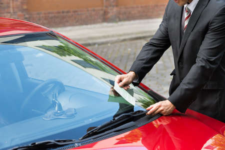 illegally: Close-up Of A Man Holding A Parking Ticket Placed On Car Windscreen