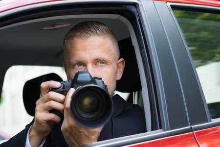 při pohledu na fotoaparát: Close-up mužské Driver Snímkování s zrcadlovka z auta