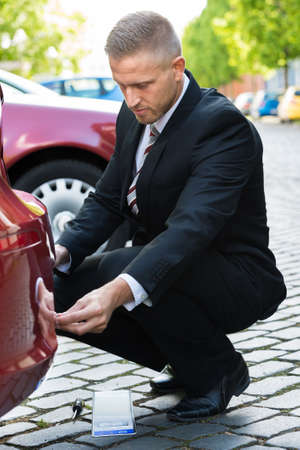 number plate: Man Placing New Empty White Number Plate On His Red Car