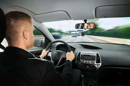 driving: Rear View Of A Young Businessman Driving Car