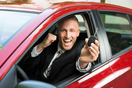 llaves: El hombre de negocios emocionada que se sienta en un coche que muestra Nueva llave del coche