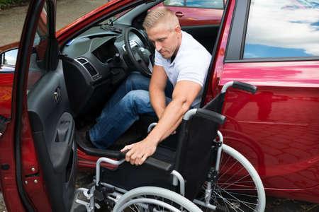 Ritratto di un driver per disabili auto con una sedia a rotelle Archivio Fotografico