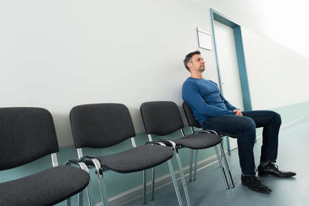 病院の椅子に座って半ば大人の男のポートレート