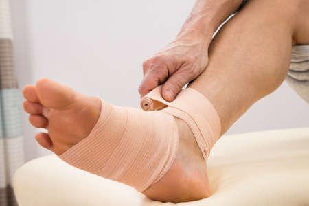 manos y pies: Primer plano de un hombre Poner elástico vendaje en su pie lesionado