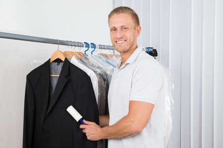 lint: Young Happy Man Cleaning Dust With Lint Roller Of Coat In Clothes Store