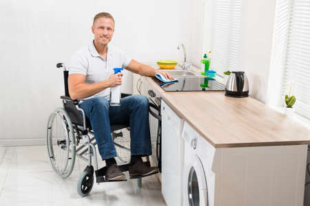 household accident: Young Happy Man On Wheelchair Cleaning Induction Stove In Kitchen Room