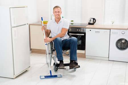 household accident: Young Happy Handicapped Man On Wheelchair Mopping Floor In Kitchen