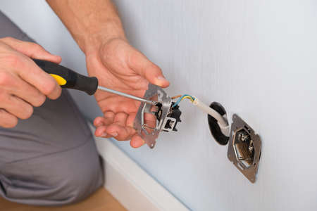 Close-up Of Electrician Hands With Screwdriver Installing Wall Socket Фото со стока