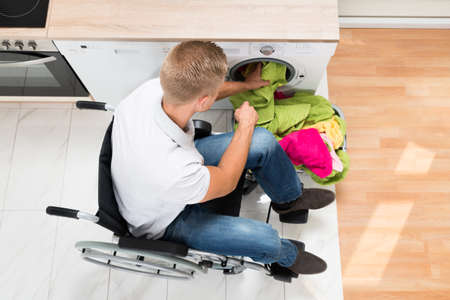 man laundry: Young Man On Wheelchair Putting Laundry Into The Washing Machine