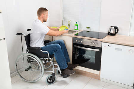 Young Disabled Man On Wheelchair Washing Dishes In The Kitchen