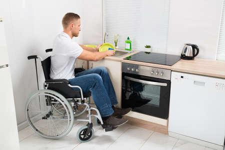 personen: Jonge gehandicapte man op rolstoel afwas in de keuken
