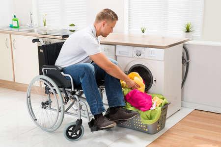 discapacidad: Hombre joven en silla de ruedas para discapacitados poner toallas en la lavadora