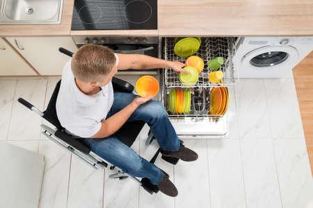 discapacidad: Vista elevada del hombre joven que personas de movilidad reducida en la cocina Foto de archivo