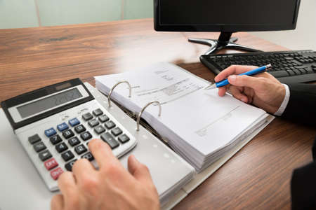 Close-up Of A Businessman Calculating Invoice Using Calculator At Desk In Office photo