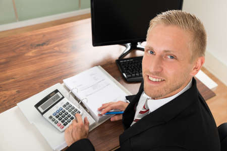 corporate finance: Portrait Of Happy Businessman Calculating Finance In Office Stock Photo