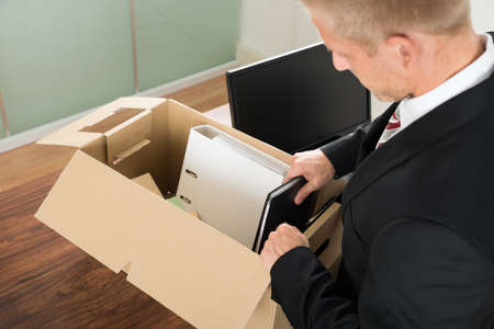 Close-up Of A Businessman Packing Files In Cardboard Box At Office