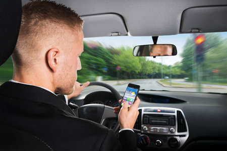 Close-up Of A Businessman Using Cellphone While Driving Car