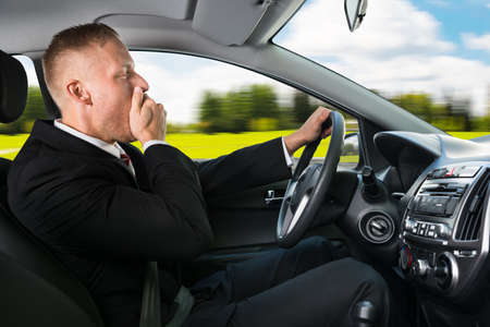 tired businessman: Portrait Of A Young Businessman Yawning While Driving Car Stock Photo