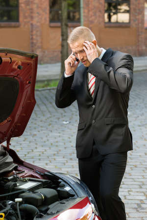 engine bonnet: Stressed Young Man Calling On Cellphone For Service With His Breakdown Car