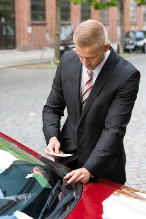 parking ticket: Portrait Of A Man Removing Parking Ticket On Car Windscreen
