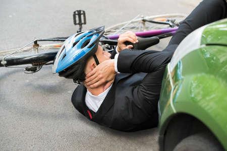 ciclista: Ciclista Masculino Con el dolor de cuello que miente en la calle Despu�s de Accidente de tr�fico Foto de archivo