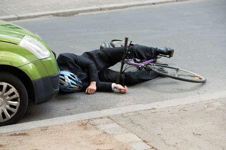 ciclista: Inconsciente Ciclista Hombre Acostado En El Camino Despu�s de Accidente de tr�fico