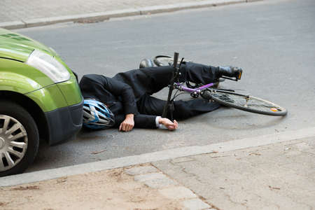 accident car: Unconscious Male Cyclist Lying On Road After Road Accident