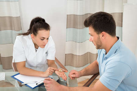 Young Female Doctor Showing Hearing Aid To Male Patient In Clinic