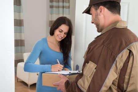hombre escribiendo: Mujer joven que firma Mientras Recibe Courier De Delivery Man At Home Foto de archivo