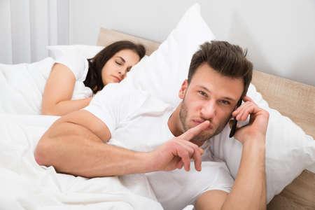 romantik: Man talar privat på mobiltelefon medan hans fru sova i sängen Stockfoto