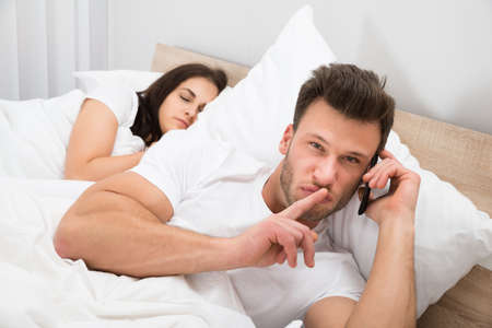 Man Talking Privately On Cellphone While His Wife Sleeping On Bed