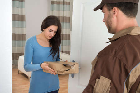 Woman Shouting On Delivery Man For Damaged Package At Doorway Stock Photo