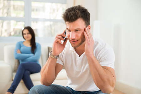 house wife: Wife With Curiosity Looking At Husband Talking Privately On Cellphone Stock Photo