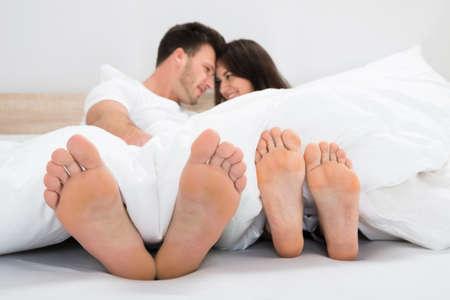 mujer hombre: Pareja sonriente rom�ntica con los pies desnudos en la cama