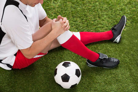 Male Soccer Player Suffering From Injury In Knee At Field photo