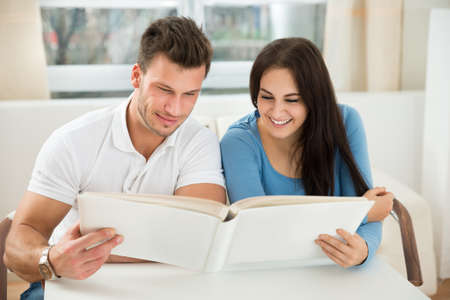 Happy Young Couple Leaning On Table Holding Green House Model